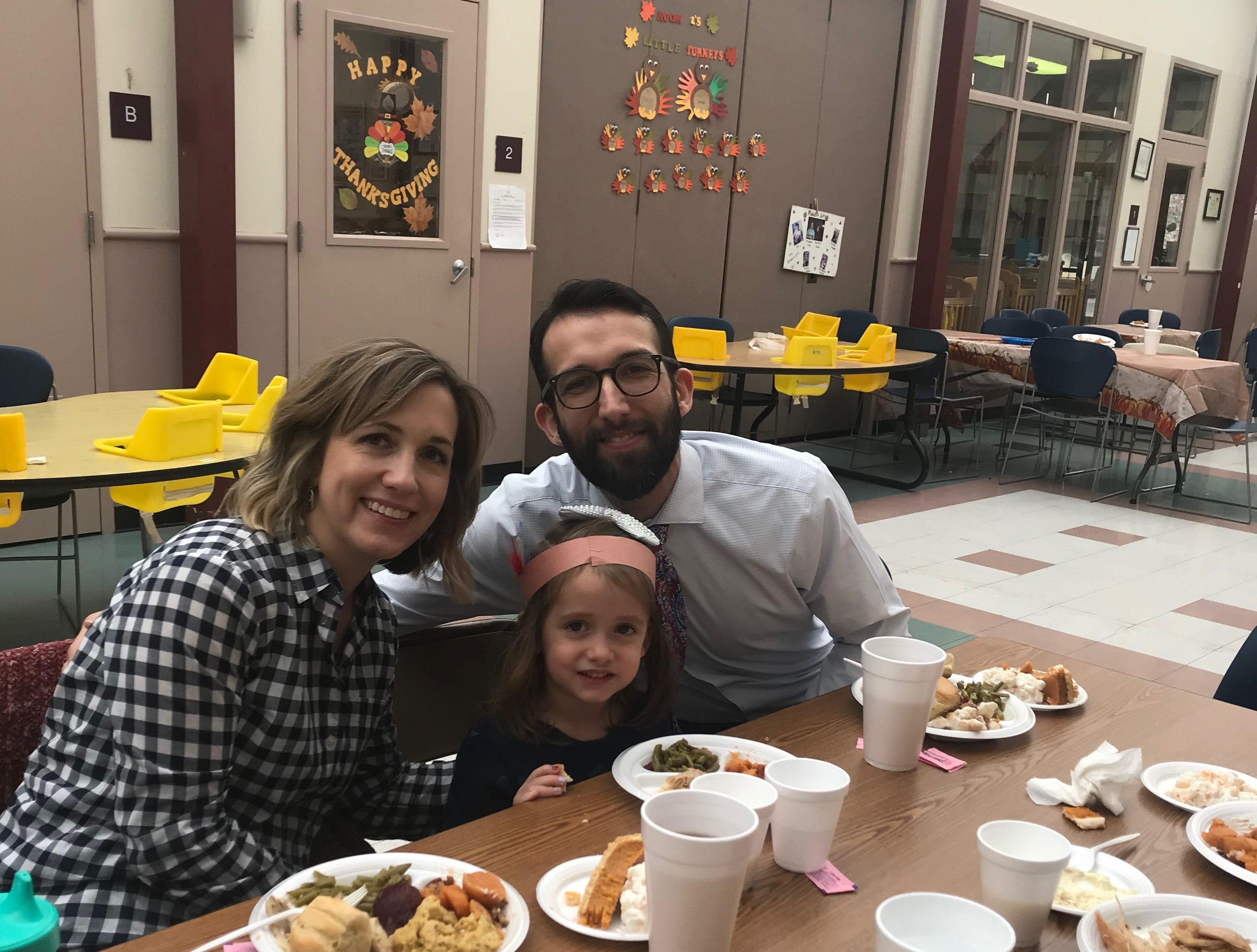 Rachel and Zach Reyes, with their daughter, Aidy, enjoy a Thanksgiving lunch at the Day Nursery of Abilene's Cedar.