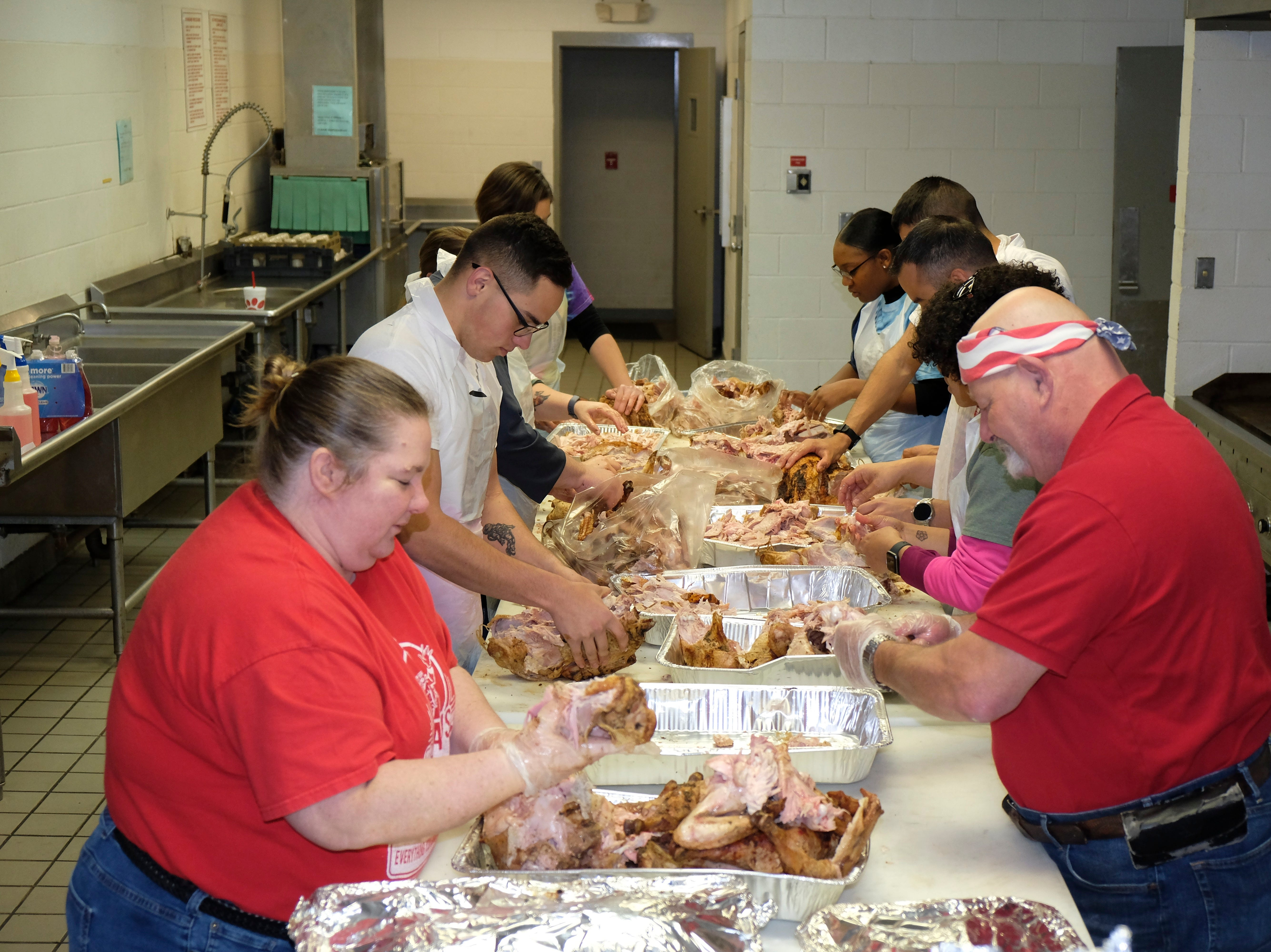 Dyess We Care Team volunteers and sponsors hard at work preparing the meal for the Veterans Thanksgiving Dinner.