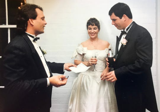 Jacob Murphy, left, presents the wedding certificate to newly married Grace and John Boyle.