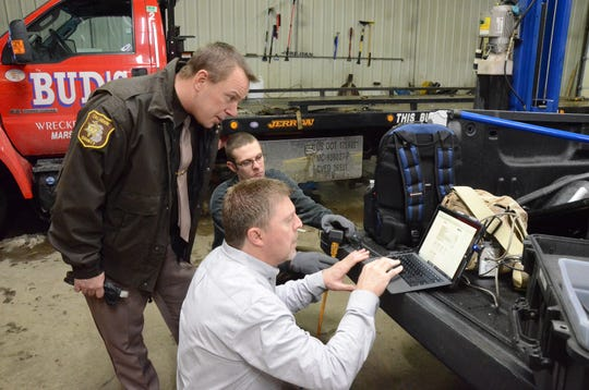Detective Sgt. Steve Hinkley, front to back, and deputies Brian Weberling and Ben Hess look at information Friday from a crash data recorder.