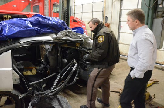 Deputy Brian Weberling, left, and Detective Sgt. Steve Hinkley inspect the damaged car.