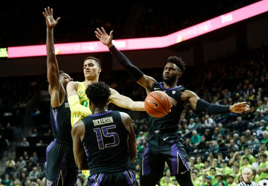 Oregon guard Will Richardson (0) passes the ball against Washington defenders, including Noah Dickerson (15), during an NCAA college basketball game Thursday, Jan. 24, 2019, in Eugene, Ore. (AP Photo/Thomas Boyd)