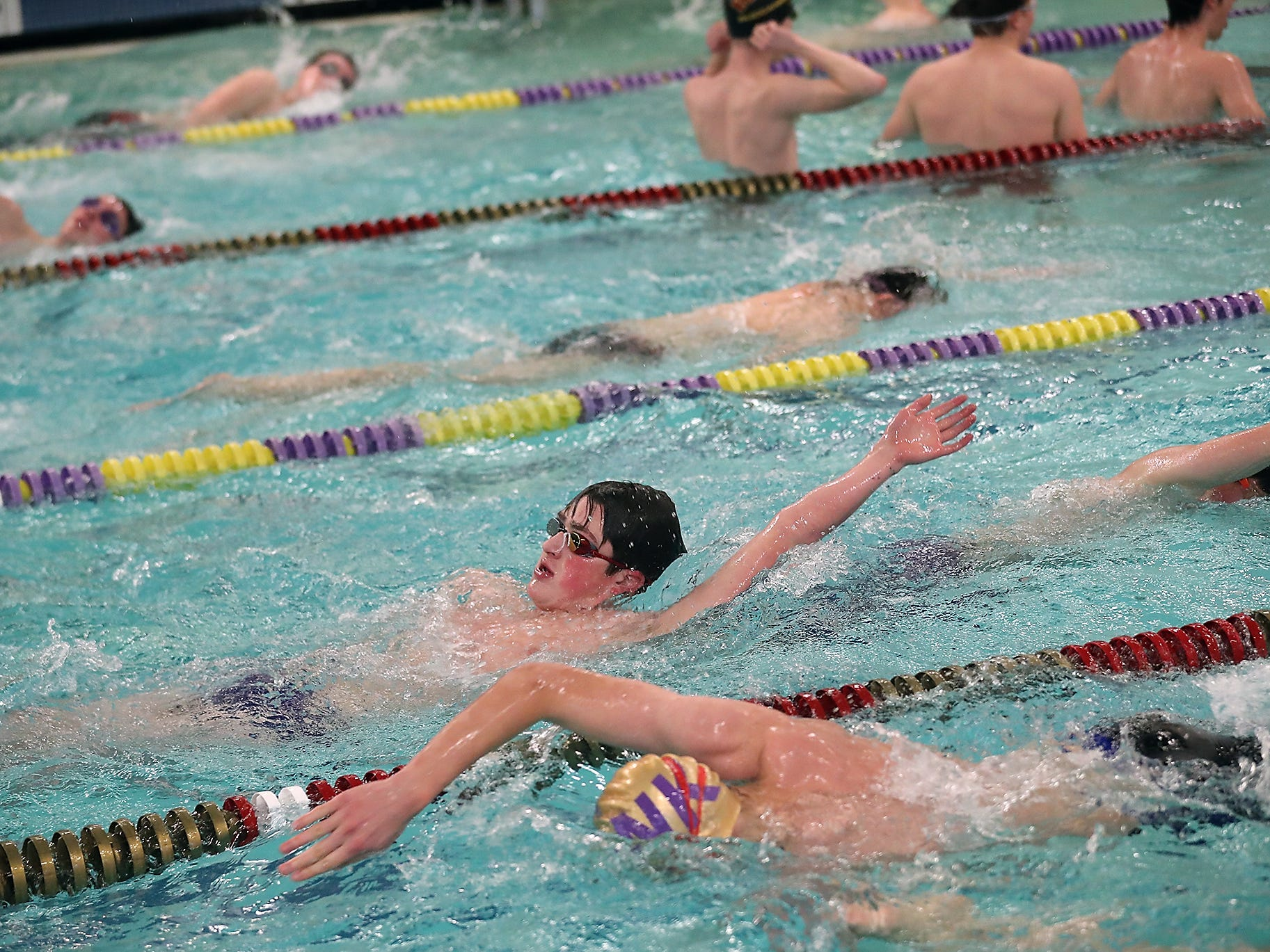 North Kitsap's Nathan Ramey (center) warms up prior to the start of their meet against Kingston on Thursday, January 24, 2019.