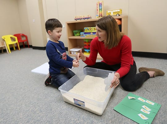 Speech Language Pathologist Beth Novak and Wyatt Tull, 4, work on the pronunciation of the letters c, k and l with an activity that allows Wyatt to find the letters buried in rice at the Early Life Speech and Language clinic in Bremerton on Friday.