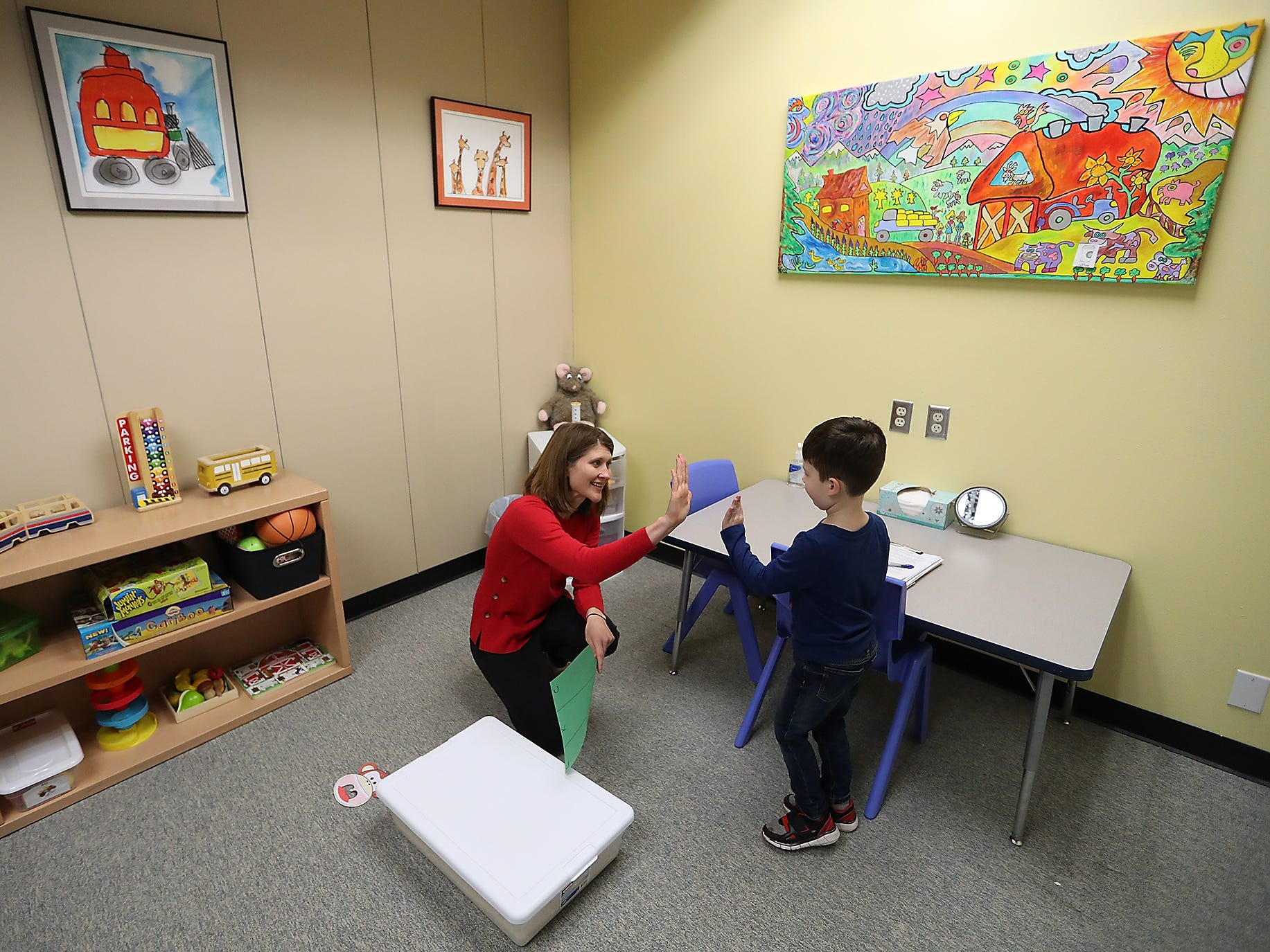 Clinic Manager / Speech Language Pathologist Beth Novak gets a high-five from Wyatt Tull, 4, at the Early Life Speech & Language clinic in Bremerton on Friday, January 25, 2019.