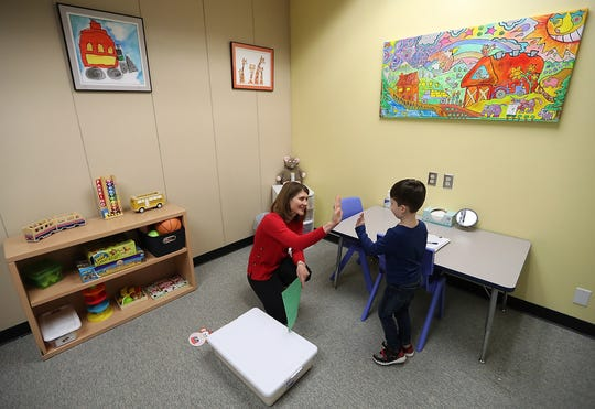 CSpeech Language Pathologist Beth Novak gets a high-five from Wyatt Tull, 4, at the Early Life Speech and Language clinic in Bremerton on Friday.
