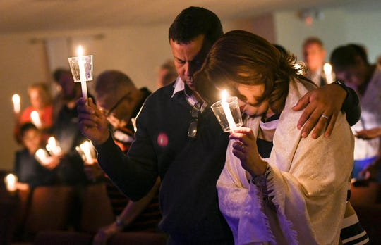 Orlando Vellon and his wife Angie hold candles at Nuevo Pacto United Methodist Church in Sebring during a memorial service in memory of Marisol Lopez and the other victims of a shooting at SunTrust Bank. Lopez was a member of the church.  Mandatory Credit: Craig Bailey/FLORIDA TODAY via USA TODAY NETWORK