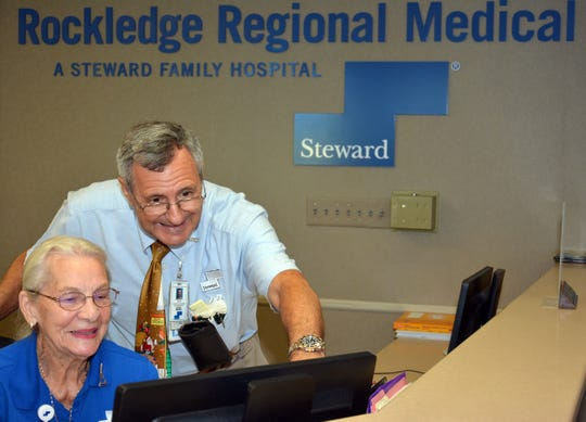 Dale Smith of Rockledge Regional Medical Center's IT department helps volunteer Betty Flatt with a computer issue.