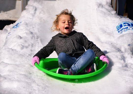 Taylor Nance comes down the slope full blast in her saucer. It was their annual Snow Day at Faith Fellowship Academy in Melbourne Friday morning and Gentleman's Ice out of Jacksonville brought their snow machine and tons of ice to make a winter wonderland for the students.