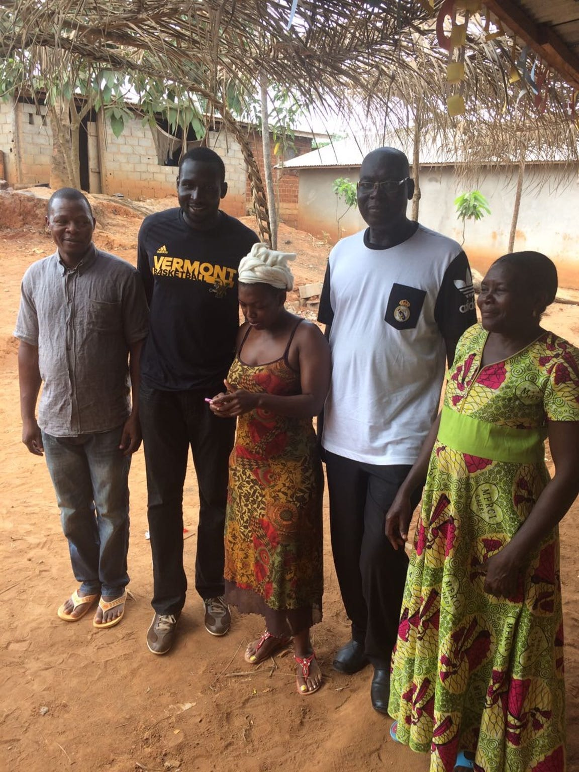 UVM basketball player Sam Dingba, second from left, poses with his father, Andre Tirmo, second from right, and others at an orphanage about  15 miles outside of Yaoundé, Cameroon.