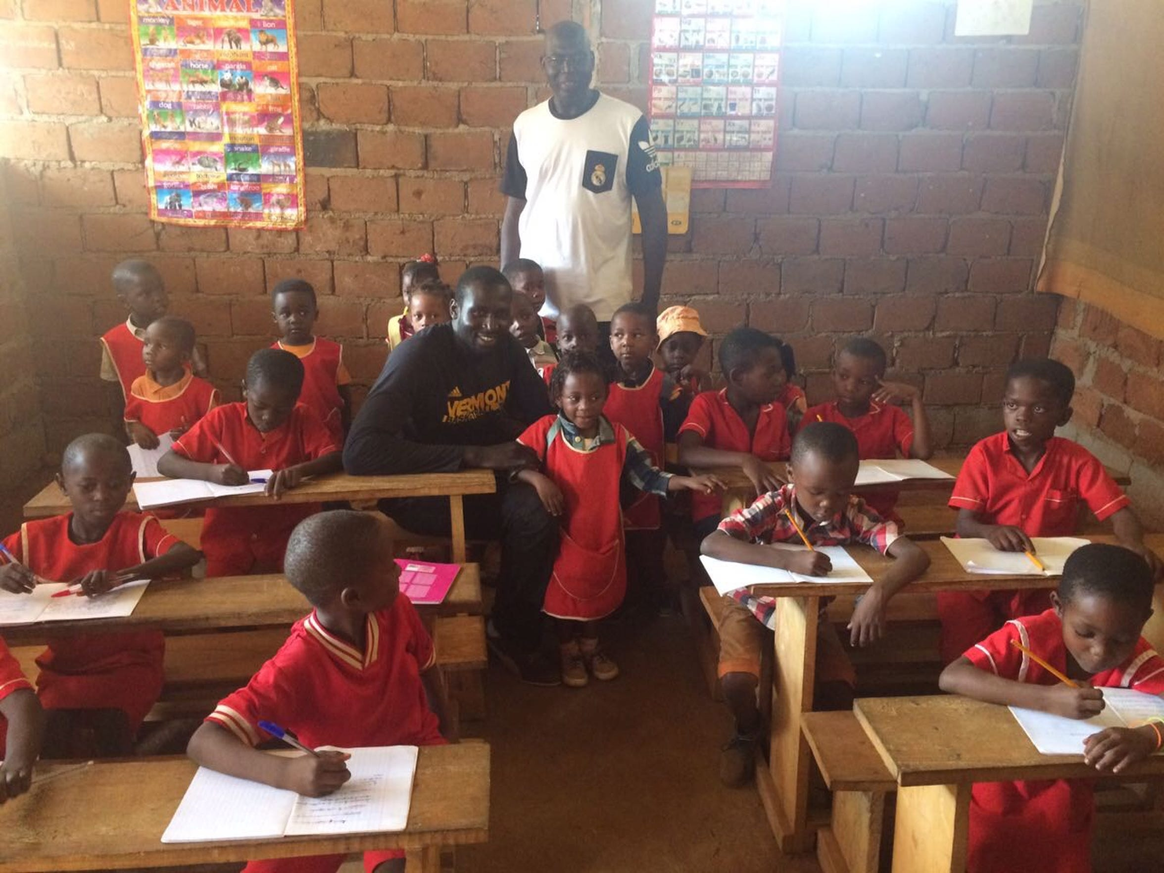 UVM basketball player Samuel Dingba sits with a group of orphans in a village classroom about 15 minutes outside of Dingba's home city of Yaoundé, Cameroon. Dingba returned to Cameroon in 2016 to donate food, clothing and other essentials.