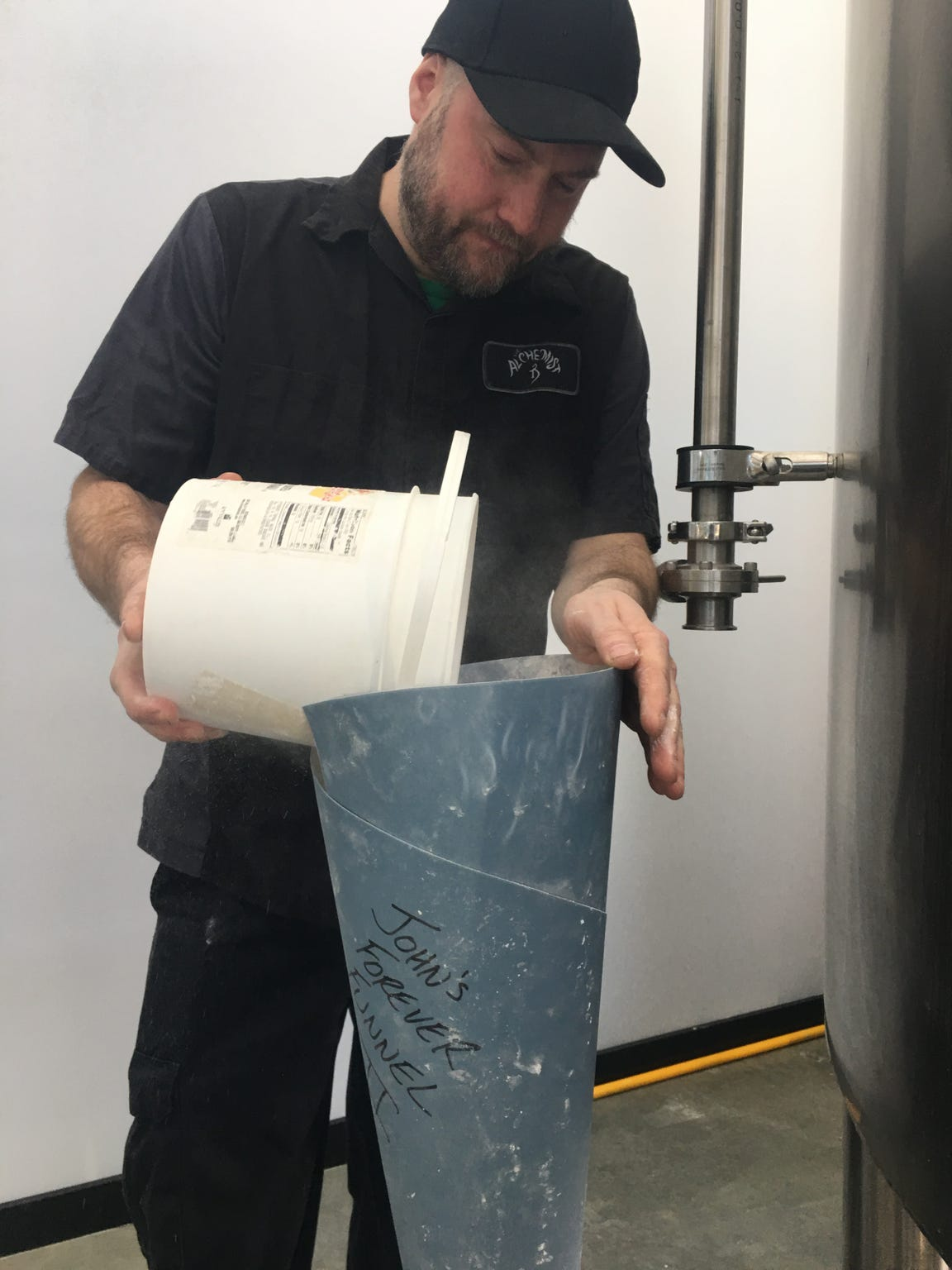 Jim Conroy pours a combination of salts into a funnel to treat the water that will be used to make a batch of Ouroboros beer at The Alchemist in Stowe on Jan. 17, 2019.