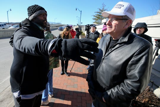 A man, left, who declined to give his name, confronts Randall Terry, a pro-life leader, far right, as he led a small group of demonstrators, demanding Diocese of Covington Bishop Roger Joseph Foys apologize for his condemnation of Covington Catholic students, Friday, Jan. 25, 2019, in front of the Covington Chancery in Covington, Ky.