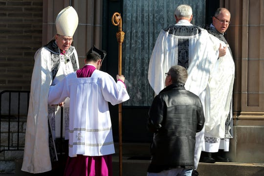 Randall Terry, a pro-life activist, center, confronts Diocese of Covington Bishop Roger Joseph Foys as he leaves a funeral ceremony. Terry demanded Foys apologize for his condemnation of Covington Catholic students, Friday, Jan. 25, 2019, in front of the Covington Chancery in Covington, Ky.