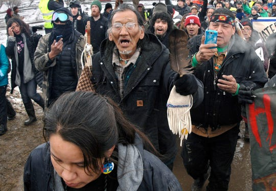 In this Feb. 22, 2017, file photo, a large crowd representing a majority of the remaining Dakota Access Pipeline protesters, including Nathan Phillips, center with glasses, march out of the Oceti Sakowin camp before the deadline set for evacuation of the camp near Cannon Ball, N.D.