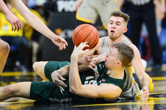 Michigan State's Thomas Kithier and Iowa's Jordan Bohannon fight for a loose ball during the first half.