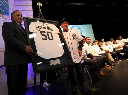 Detroit Tigers' Al Avila (left), executive vice president of baseball operations and general manager, and Novi mayor Bob Gatt, unveil a Tigers jersey that the Tigers gave the city in honor of their 50th anniversary of being a city. The Novi Civic Center hosted during the 2019 Detroit Tigers Winter Caravan on Thursday, Jan. 24, 2019.
