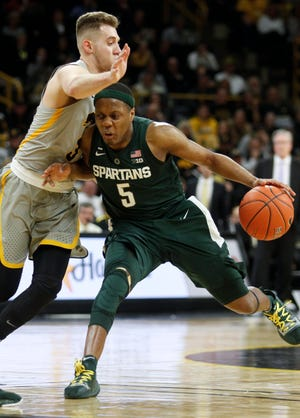 Cassius Winston of the Michigan State Spartans drives down the court in the second half against guard Jordan Bohannon of the Iowa Hawkeyes.