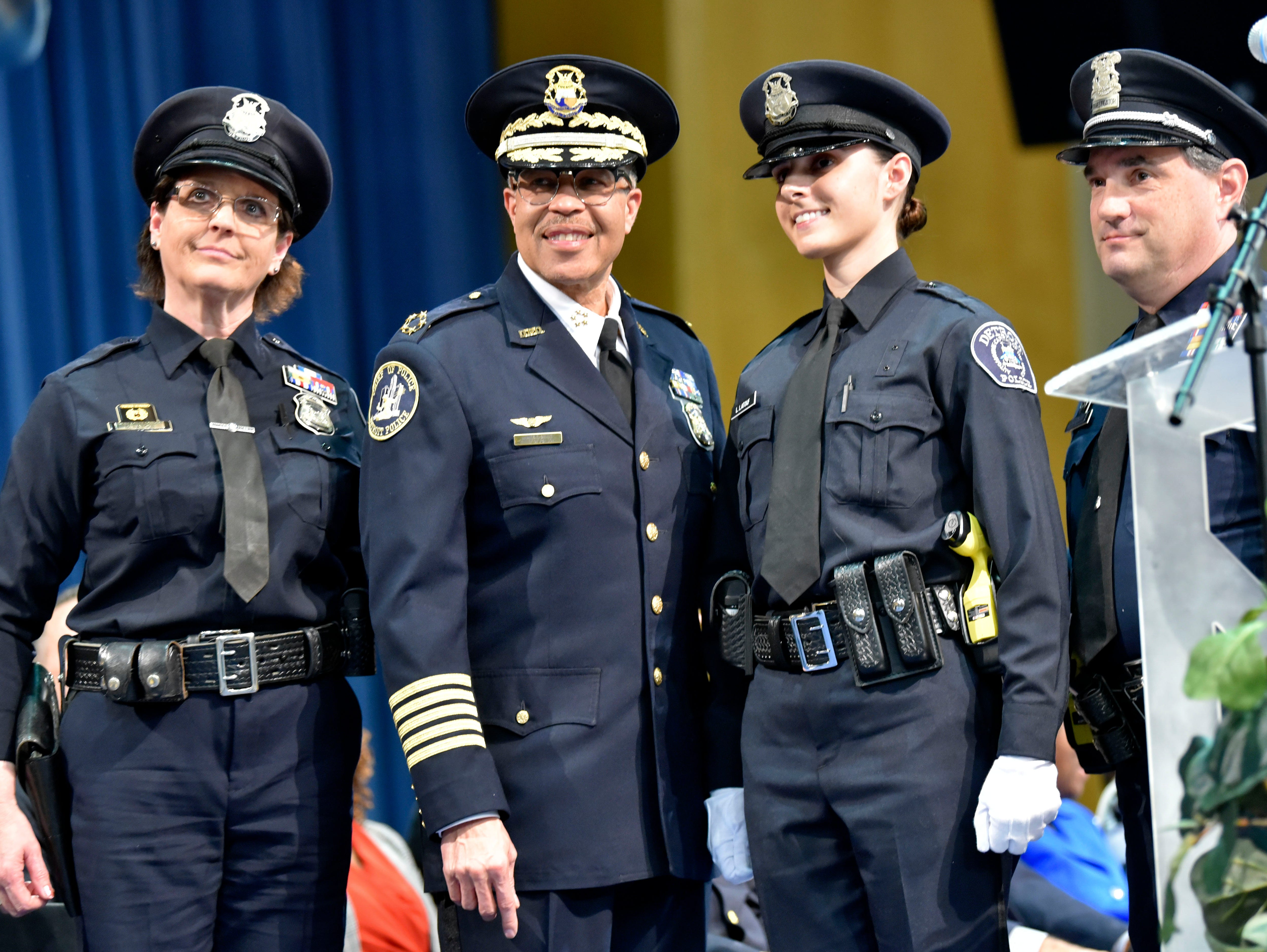 After being presented with her badge by Police Chief James Craig, second from left, newly sworn officer Lisa Latouf poses with her mother, Detroit Police Officer Donna Latouf, left, and uncle, Detroit Police Investigator Tim Ewald.