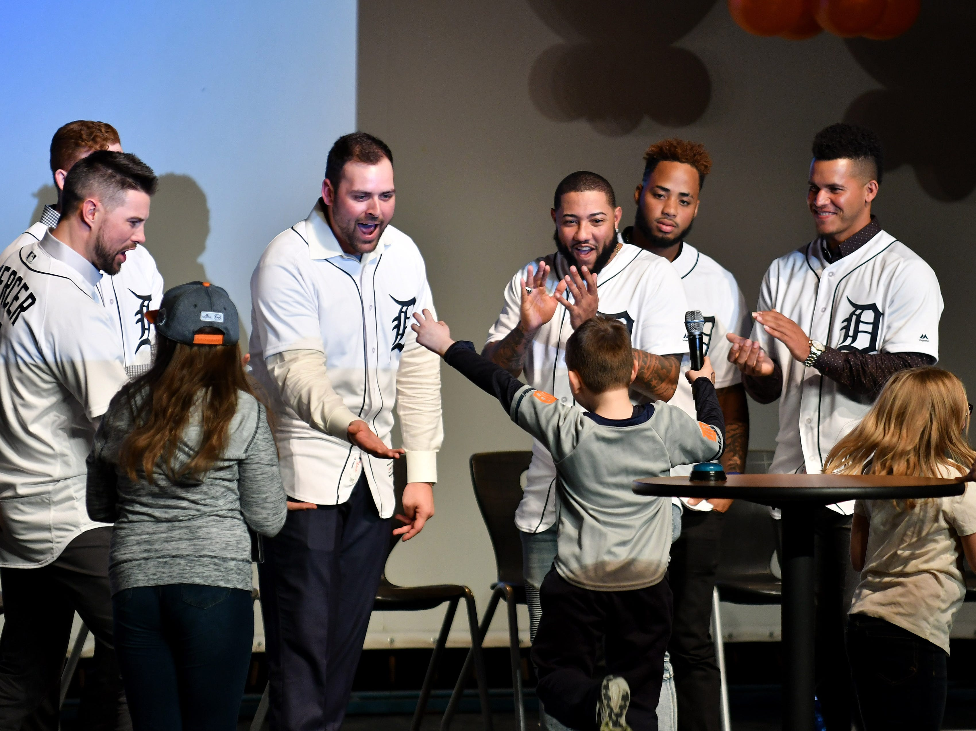 Tigers pitcher Michael Fulmer, second from left, and other Tigers high five James MacFarlane, 6, of Milford while they play a Tigers trivia game at a kids rally at Novi High School.