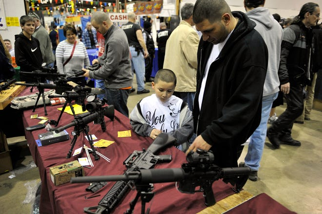 Various AR-15 semi-automatic rifles are seen on a vendor's table during the Gun and Knife Show at the Gibraltar Trade Center in Taylor in 2013.