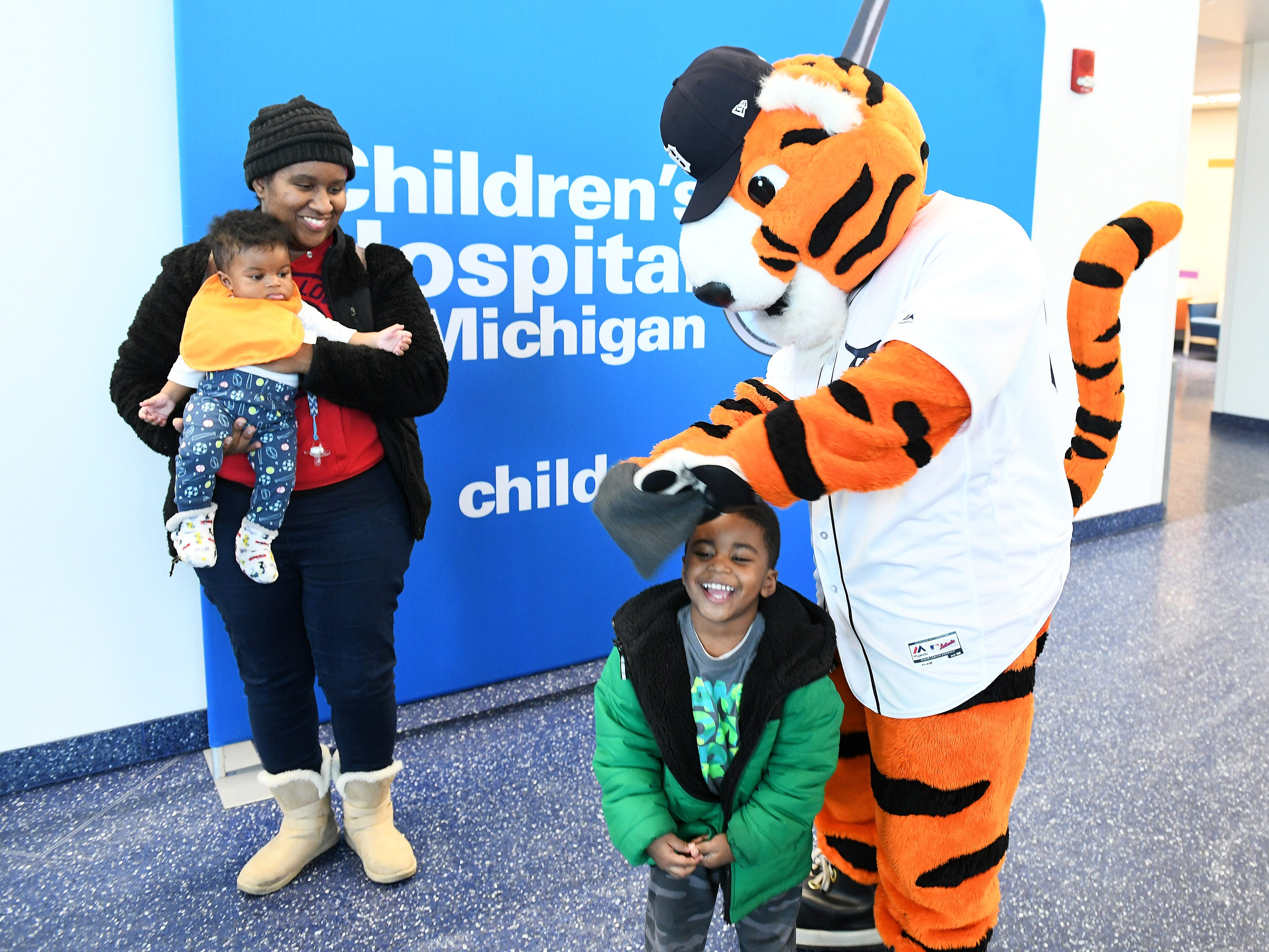 Paws plays with the hat of Domani Dixon, 3, with his mom, Demetria Dixon, left, and Maxwell Dixon, 6 months, at the Children's Hospital of Michigan.