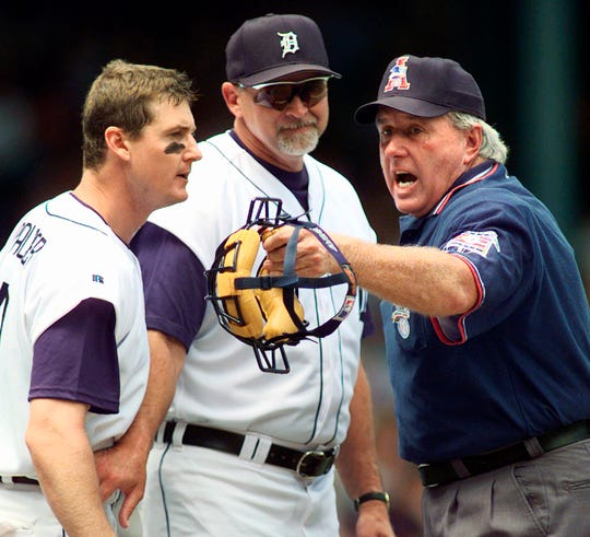 In this July 22, 1999 photo, Detroit Tigers' Dean Palmer, left, continues to argue with home plate umpire Jim McKean, right, as manager Larry Parrish holds Palmer back in the second inning of their game against Kansas City in Detroit. McKean, who umpired 10 no-hitters and three World Series during a big league career from 1973-99, has died. He was 73.