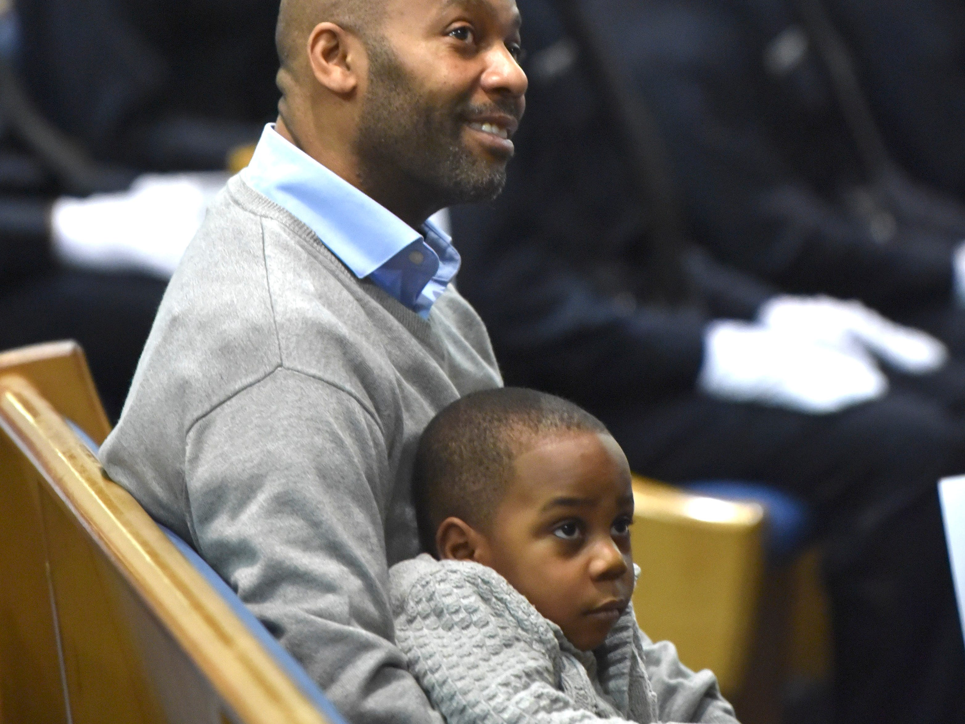 Robert Mosley of Detroit watches the graduation of his daughter, Bianca Mosley, with son Jaxon Mosley, 3.