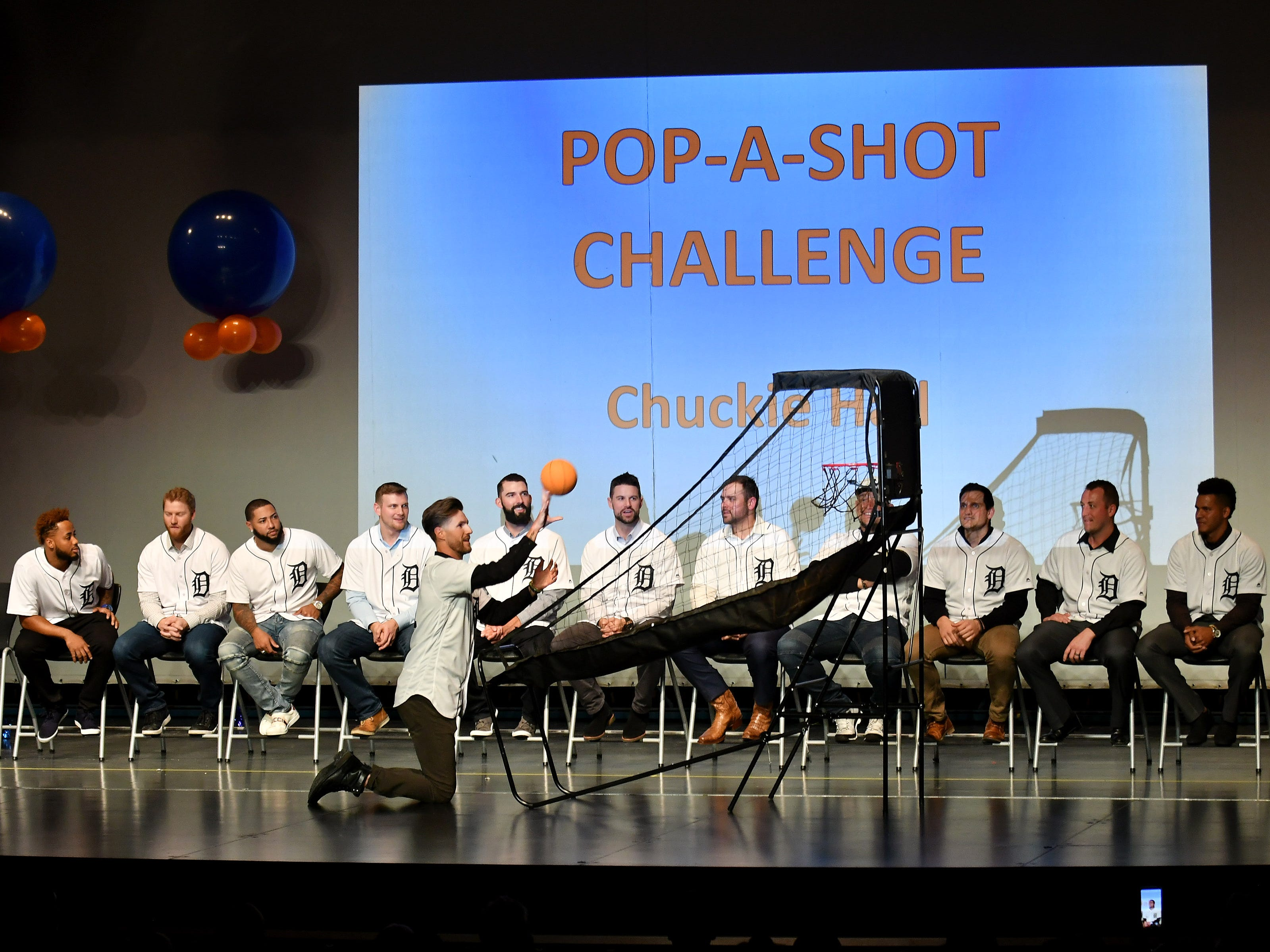 Tigers pitcher Shane Greene competes in a pop-a-shot challenge at a kids rally at Novi High School.