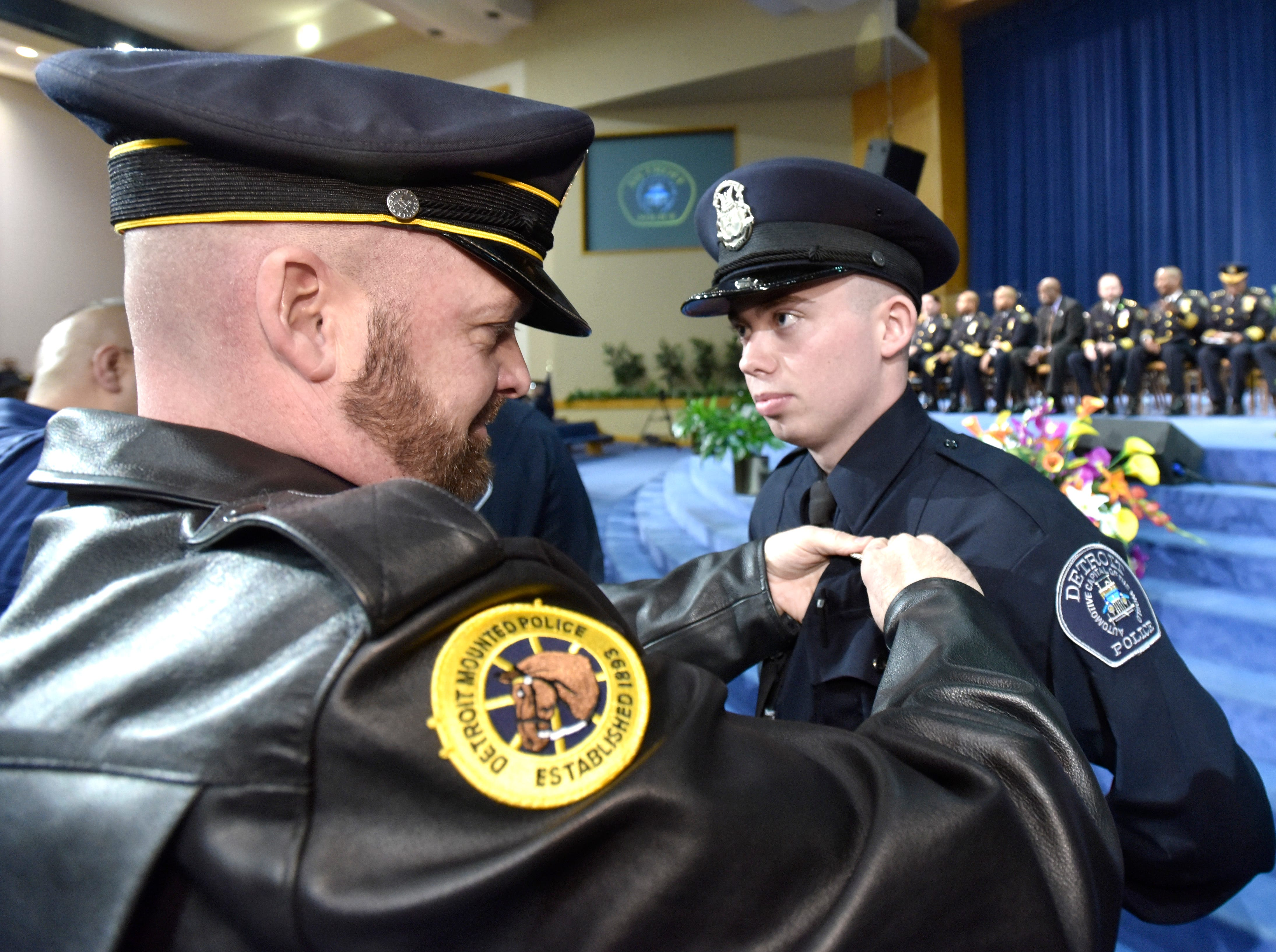 Detroit Police Mounted Unit Officer Phil Long pins a badge on the uniform of his son, Tyler Long.