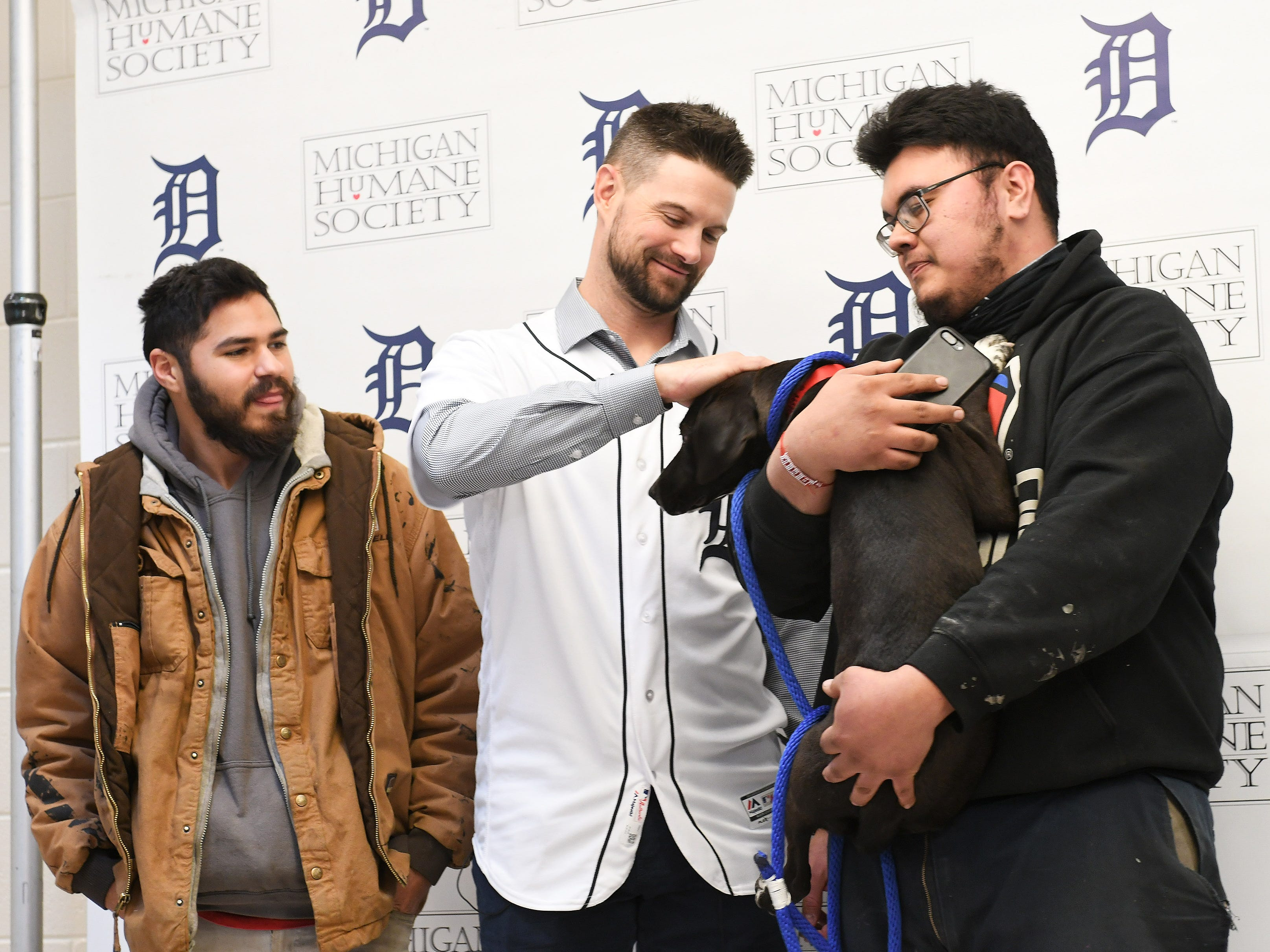 Tigers shortstop Jordy Mercer pets Lark who is being adopted by Marcelo Alvarado, 24, of Detroit, right, 25, with Marcelo's cousin, Gabriel Angel 25, left, at the Michigan Humane Society.