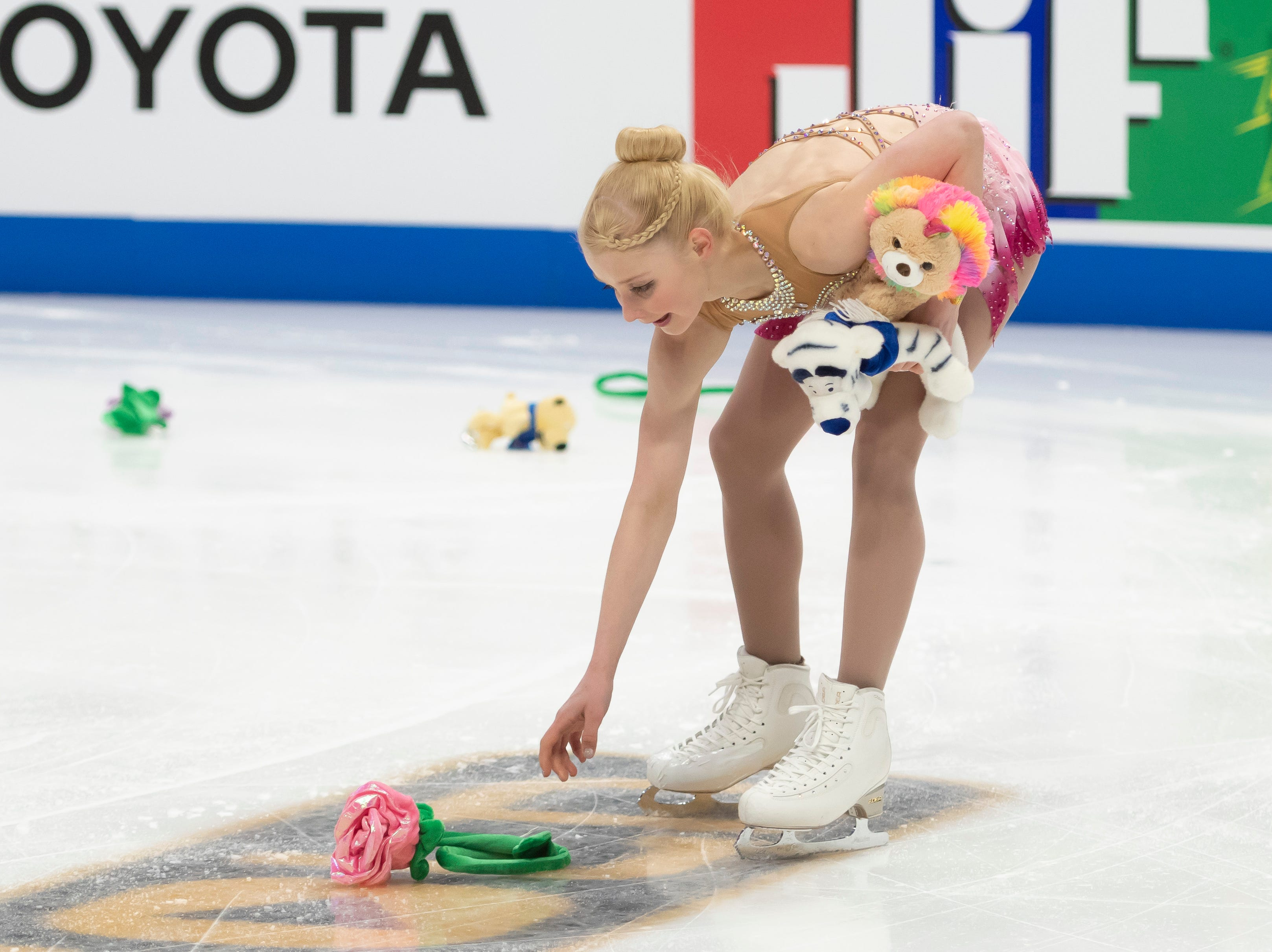 Nica Digerness picks up stuffed animals thrown onto the ice after competing in the senior pairs short program with Danny Neudecker.