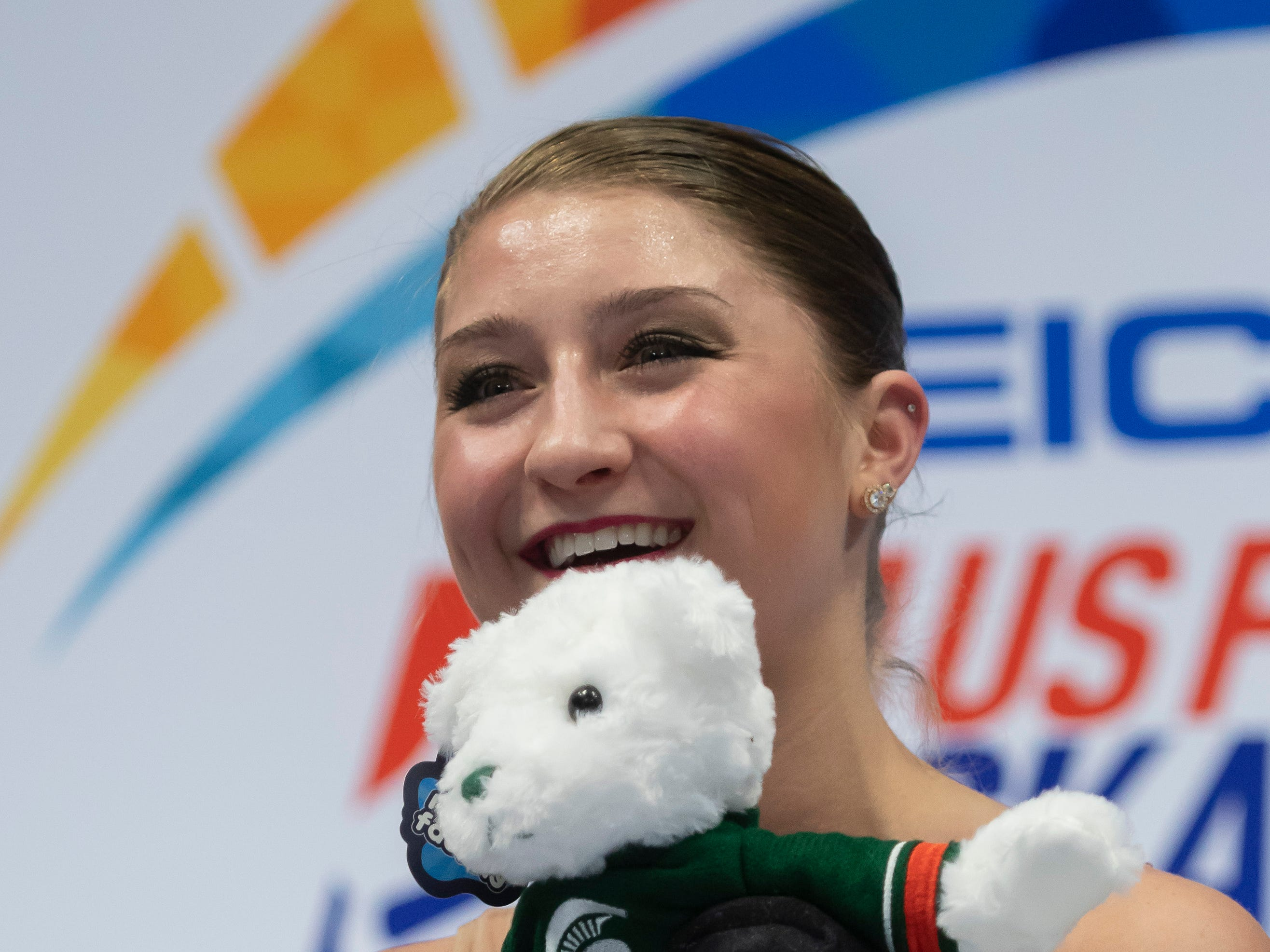 Hannah Miller, who has trained with the Lansing Skating Club, holds a Michigan State teddy bear after competing in the ladies short program.