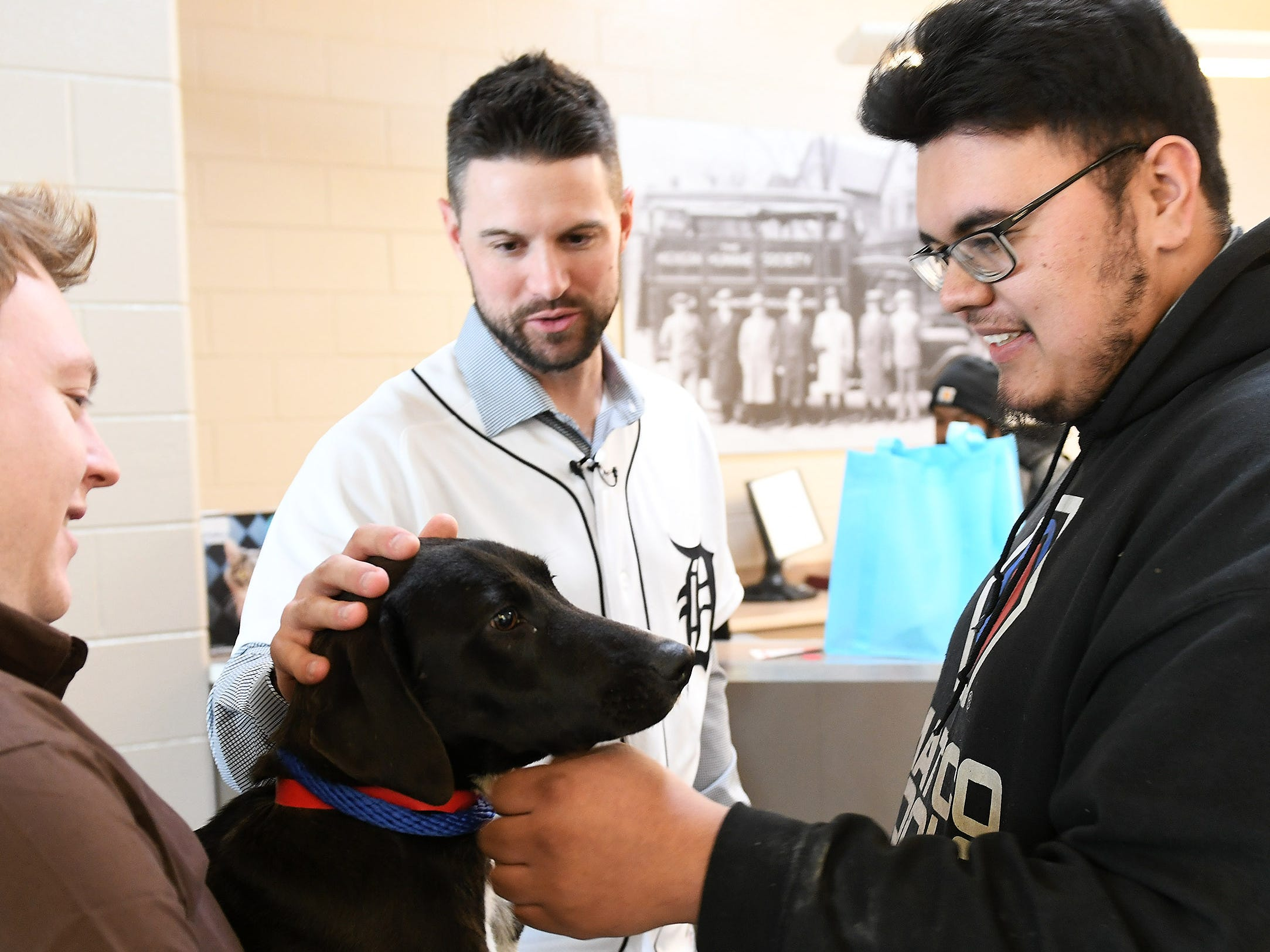While Michigan Humane Society animal transport driver Jeremy Colborn holds her, Tigers shortstop Jordy Mercer and Marcelo Alvarado, 24, of Detroit, right, pet Lark, a Labrador that Marcelo is adopting, at the Michigan Humane Society.