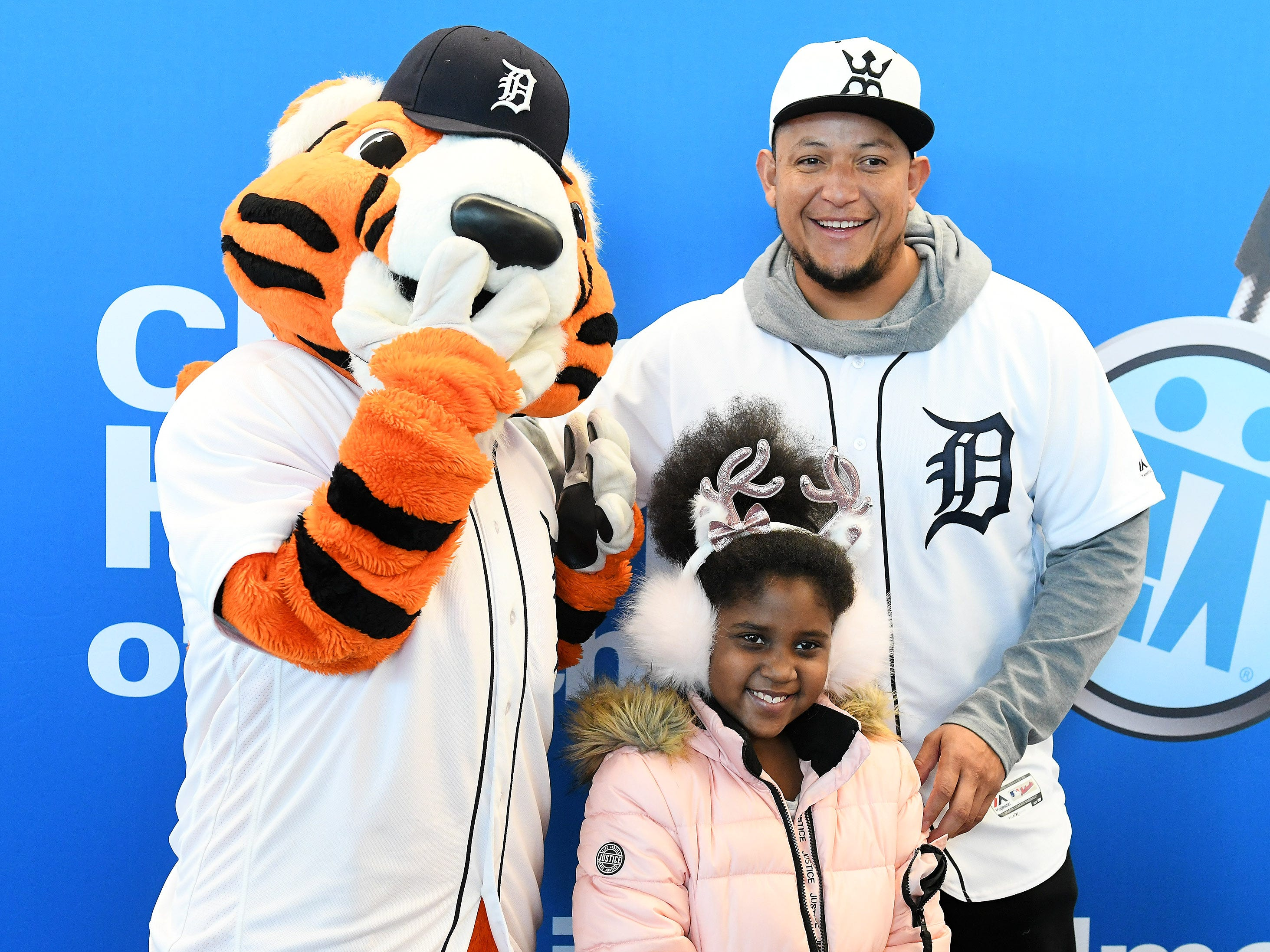 Tigers' Miguel Cabrera, right, has a photo taken with Paws and DaVeyna Perry-Stephens, 9, of Inkster who is recovering from brain surgery she had last month at the Children's Hospital of Michigan.