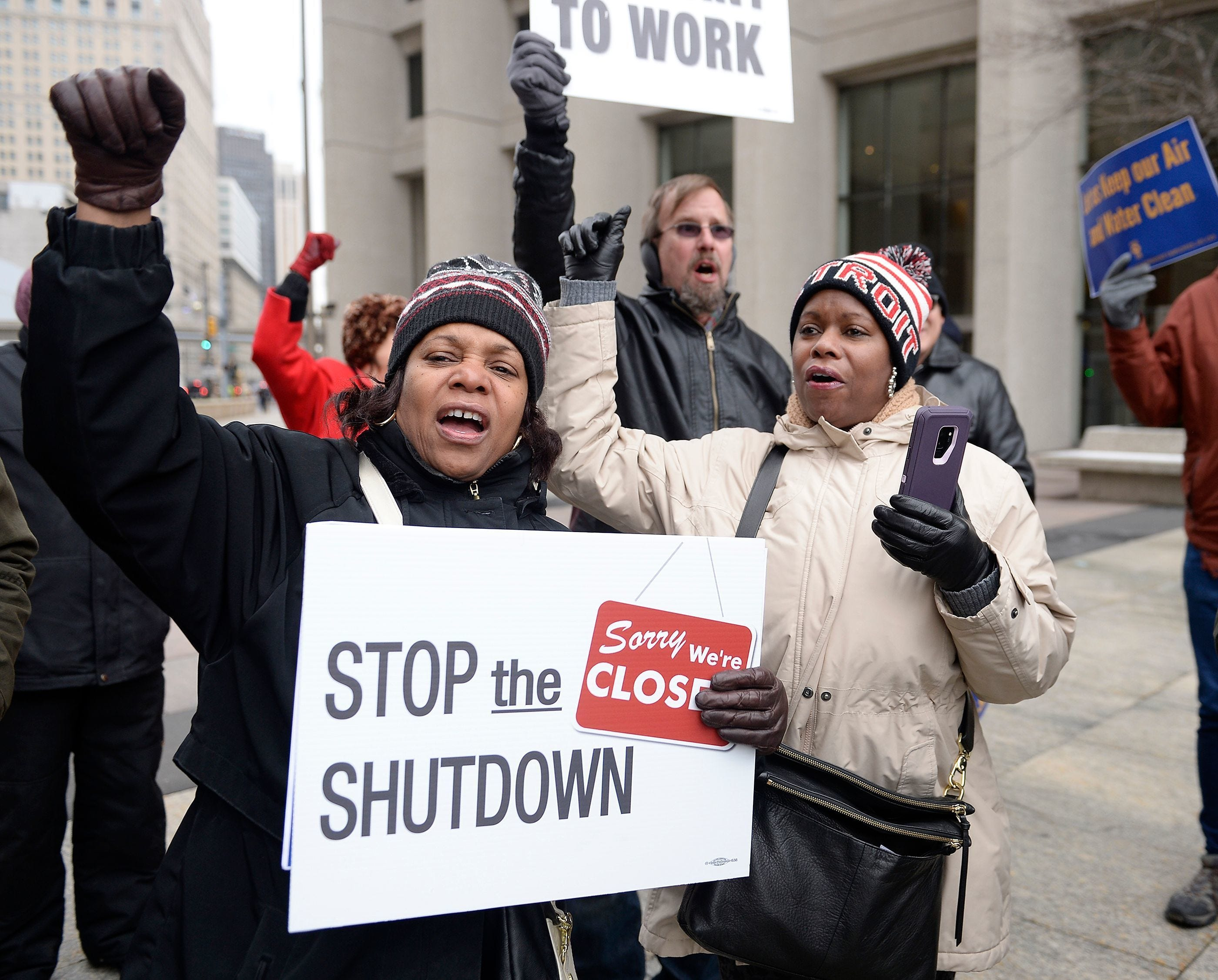 "Cheryl Monroe, left, of Ecorse, an FDA employee and her sister Sheila Monroe, right, of Fort Mill, South Carolina, a Department of Treasury employee, chant ""Call a vote"" along with other furloughed workers during an anti-government shutdown rally in downtown Detroit in this Jan. 21, 2019 file photo."