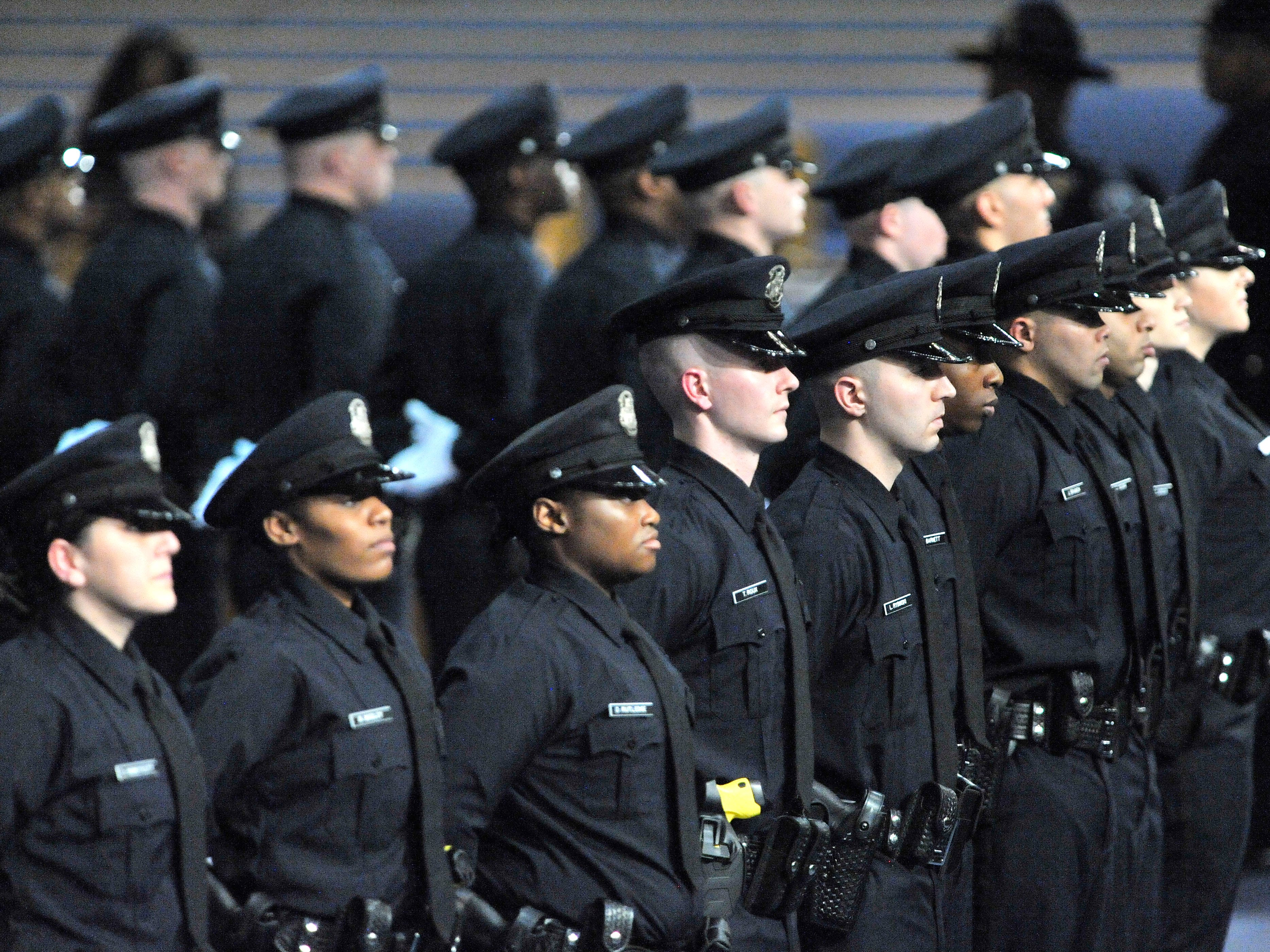 Newly sworn Detroit police officers stand at ease as they await loved ones to approach and pin police badges on their uniforms.