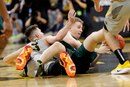 Michigan State forward Thomas Kithier fights for a loose ball with Iowa guard Jordan Bohannon, left.