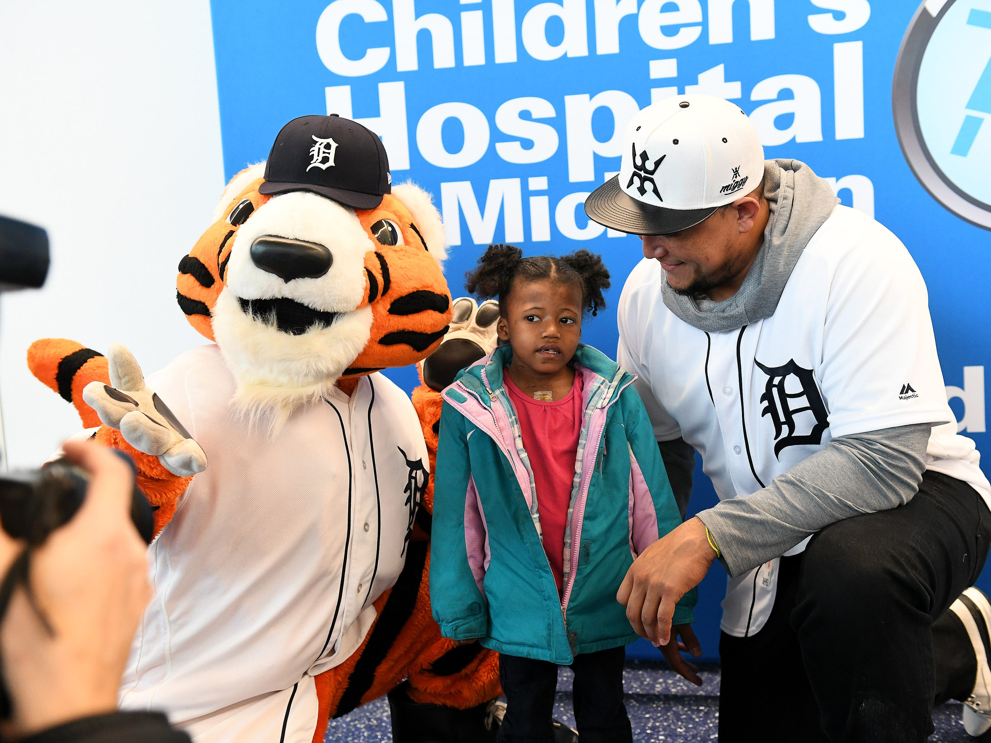 Tigers' Miguel Cabrera, right, has a photo taken with Paws and Marihanna Tillie, 5, of Detroit who is recovering from open heart surgery she had last week at the Children's Hospital of Michigan.