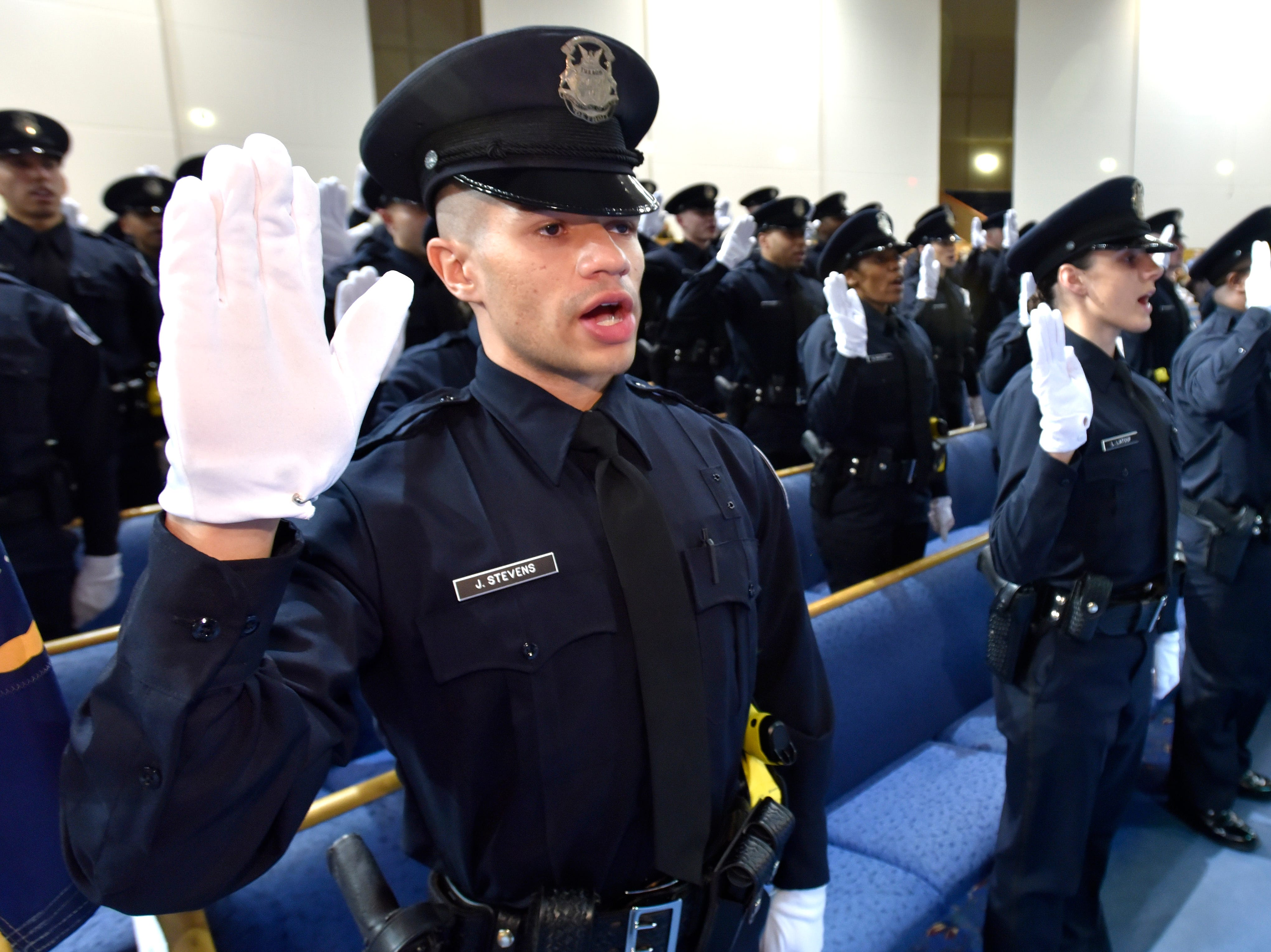 Jeremy Stevens, left, and fellow cadets take the oath to become Detroit police officers.