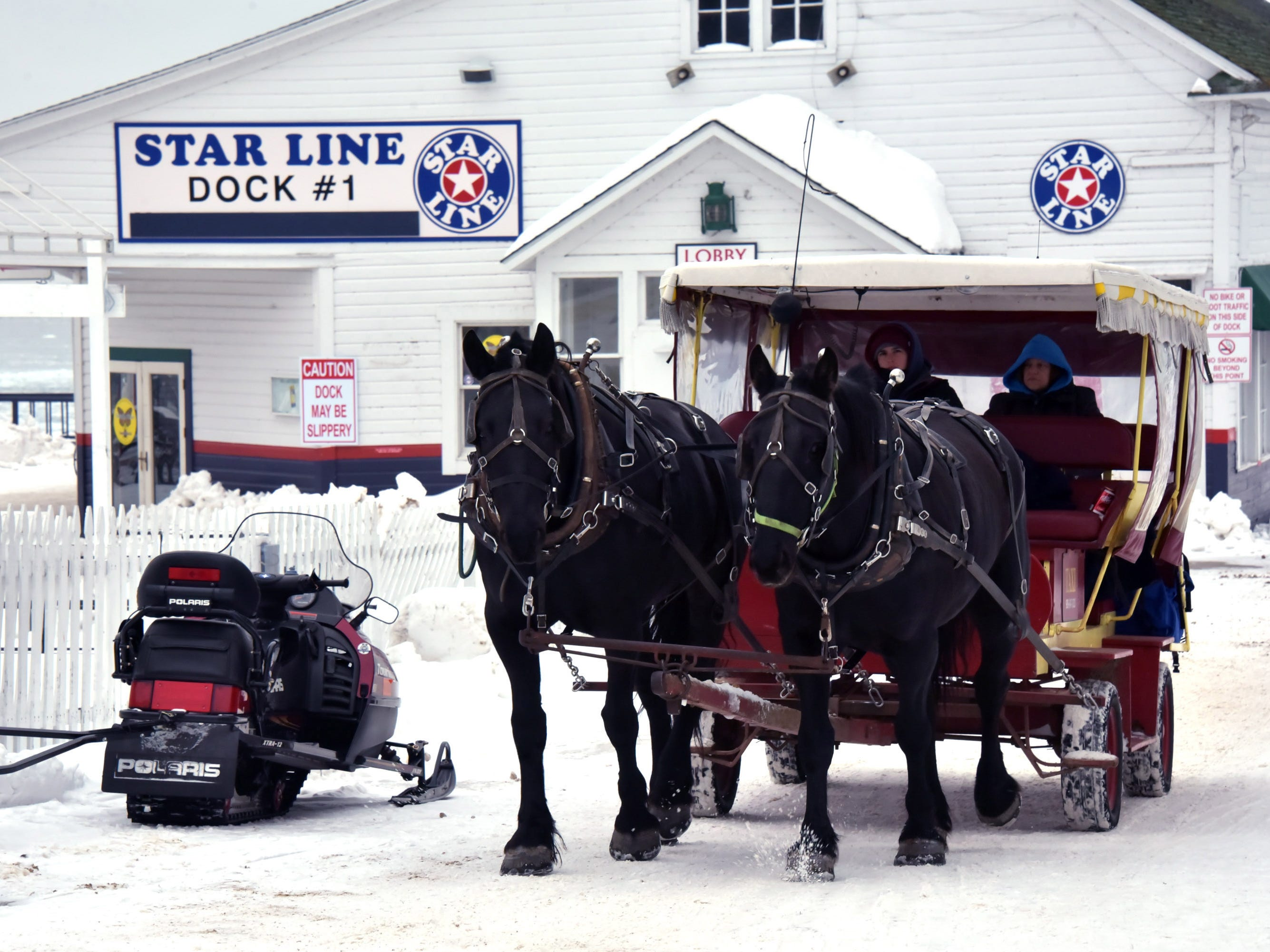 Snowmobiles or horse-drawn carriage are the best ways to get around on Mackinac Island, which is known for its Victorian homes. No automobiles are allowed.