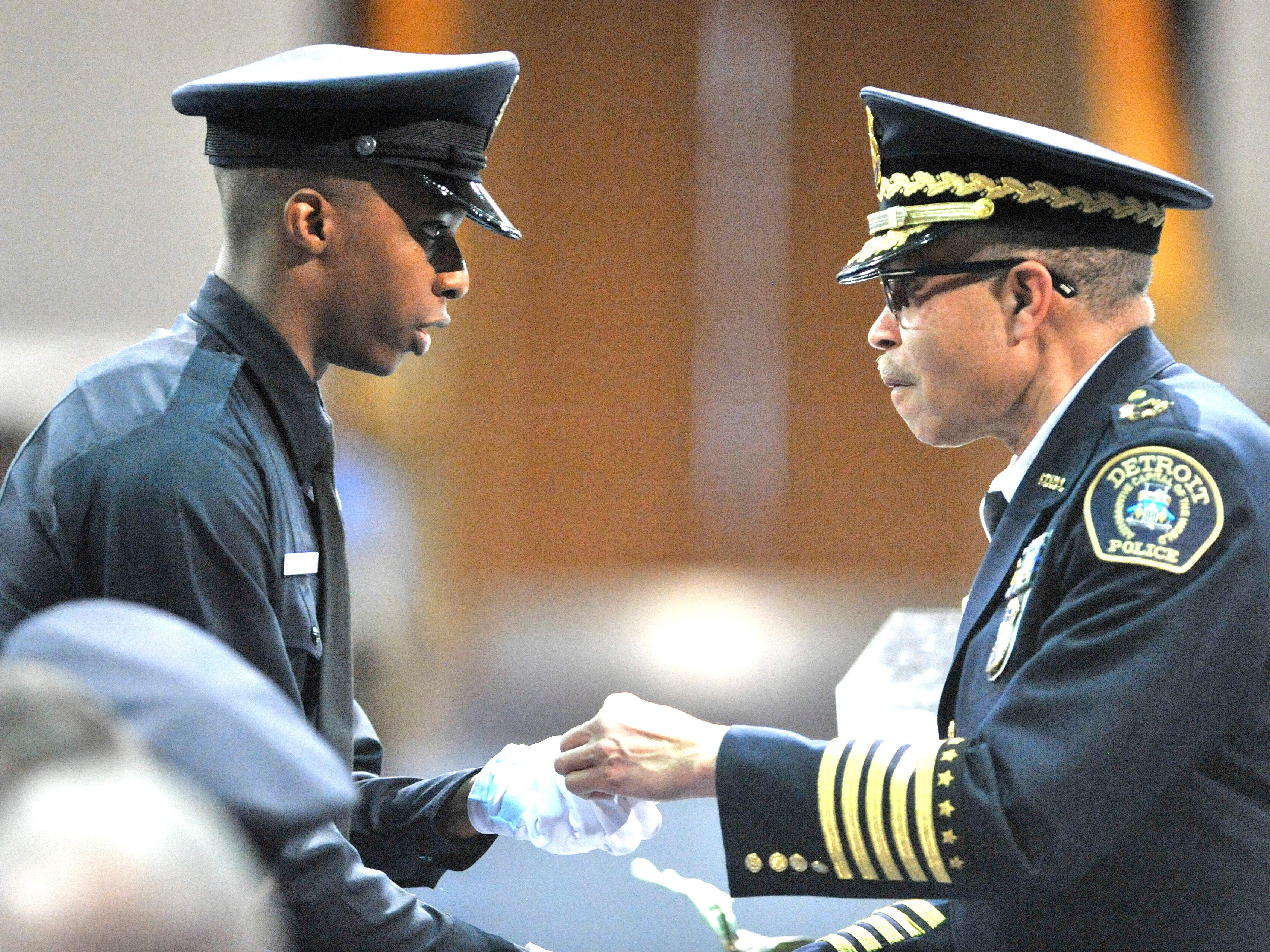 "Detroit Police Chief James Craig presents graduating police cadet Avery Barnett with his new police badge. Thirty-two cadets recited ""The Law Enforcement Code of Ethics"" and took the oath to become Detroit police officers during the Detroit Police Training Center's Basic Recruit Graduation of Class 2019-A, Friday, Jan. 25, 2019, in the sanctuary at Greater Grace Temple in Detroit."