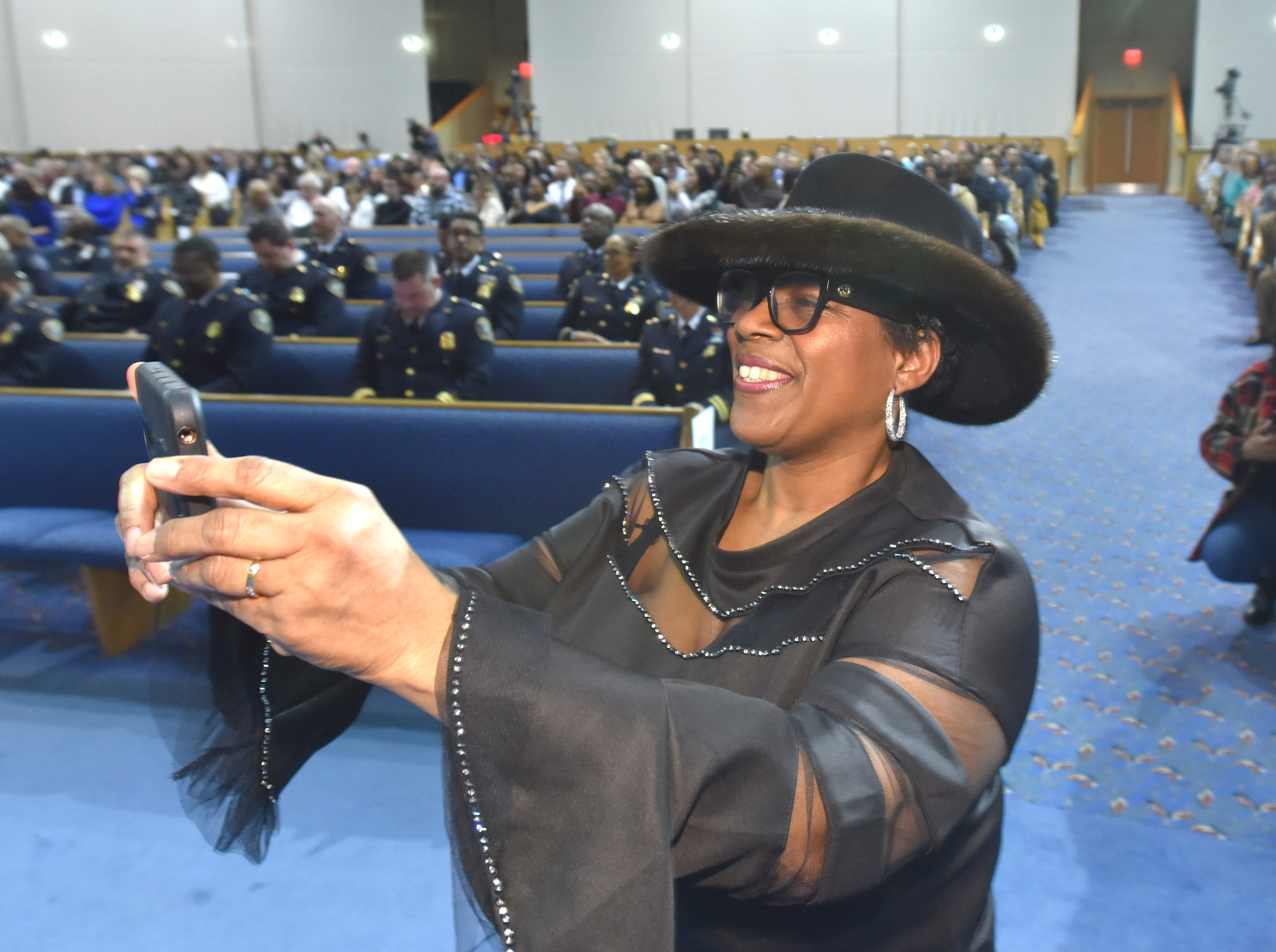 Denise Burley of Detroit takes pictures as her son, Kenneth Burley, receives his police badge.
