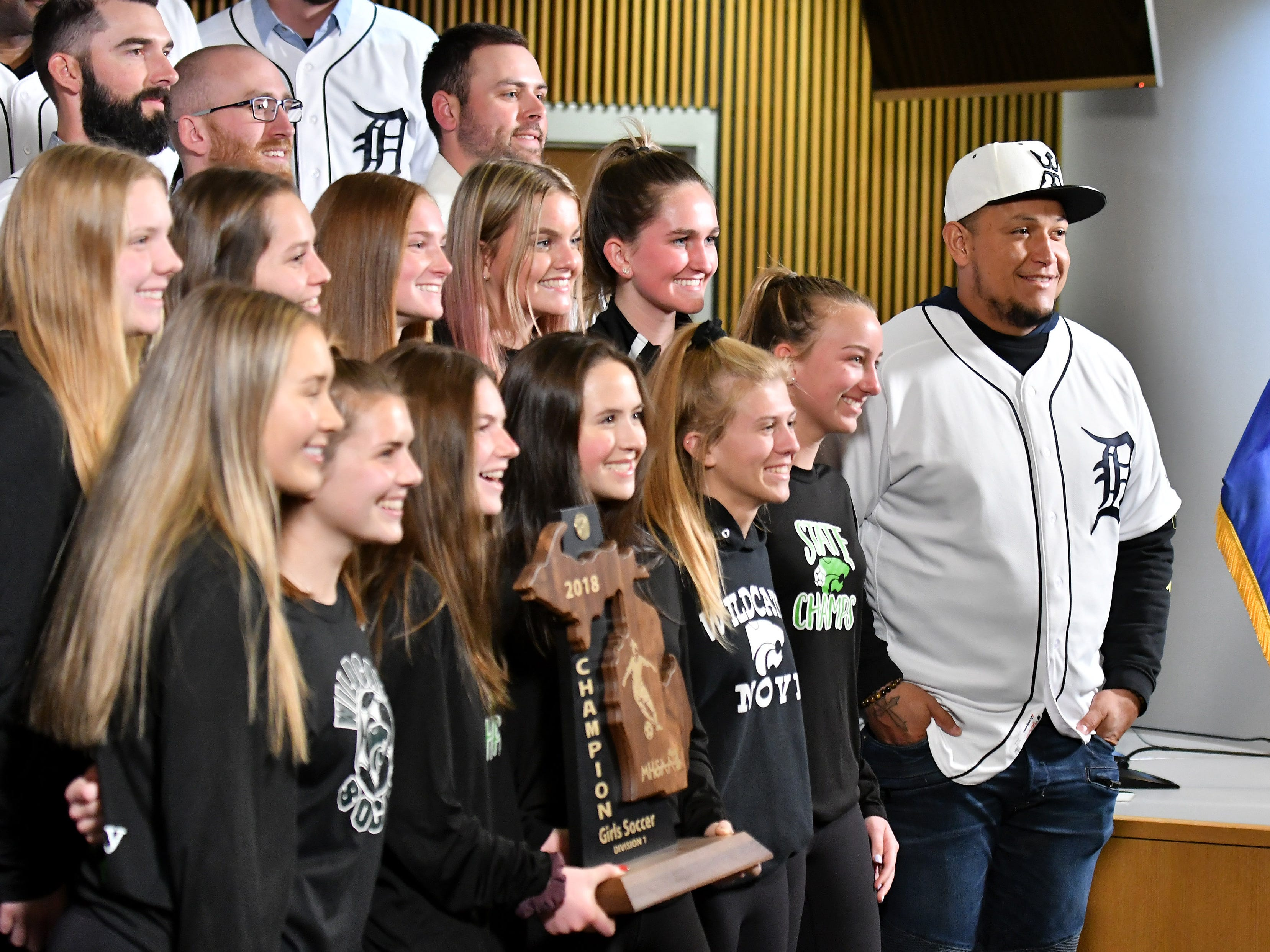 Tigers' Miguel Cabrera, right, and members of the Detroit Tigers take a group photos with some of the Div. 1 champion Novi girls soccer players at the Novi Civic Center.