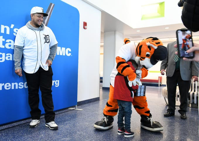 Tigers' Miguel Cabrera, left, laughs as Jesus Plata Gonzalez, 4, of Detroit goes to Paws before him during a stop on the 2019 Detroit Tigers Winter Caravan at the Children's Hospital of Michigan  in Detroit on Jan. 25, 2019.