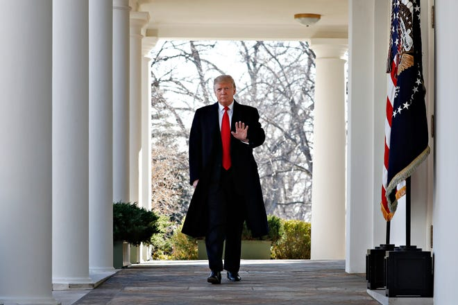President Donald Trump waves as he walks through the Colonnade  from the Oval Office of the White House on arrival to announce a deal to temporarily reopen the government, Friday, Jan. 25, 2019, from the Rose Garden of the White House in Washington.