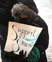 Larry Nassar survivors and others gather in the snow at the steps of the Hannah Administration Building on MSU's East Lansing campus Thursday night to mark the anniversary of his sentencing.