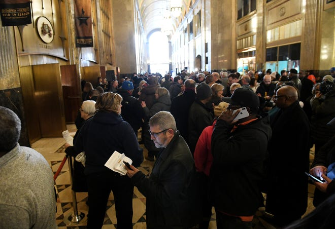 Terrence Shulman of Southfield, center, checks his phone while waiting and hoping his wristband number is called at the lobby of the Fisher Building in Detroit.