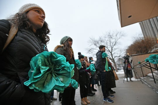 Larry Nassar survivors and others gather bearing teal flowers fashioned of tissue at the steps of the Hannah Administration Building (Woman in foreground declined when I asked her name) on MSU's East Lansing campus Thursday night to mark the anniversary of his sentencing.  The 39 attendees had planned to march across campus, but optioned to stay in place because of the weather.