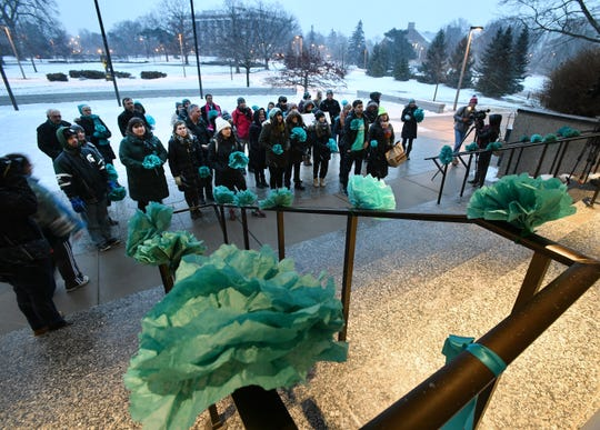 Larry Nassar survivors and others gather bearing teal flowers fashioned of tissue at the steps of the Hannah Administration Building on MSU's East Lansing campus Thursday night to mark the anniversary of his sentencing.  The 39 attendees had planned to march across campus, but optioned to stay in place because of the weather.